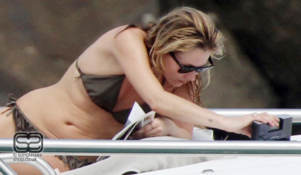 ... nothing but a skimpy bikini and a pair of Ray-Ban 2140 sunglasses.